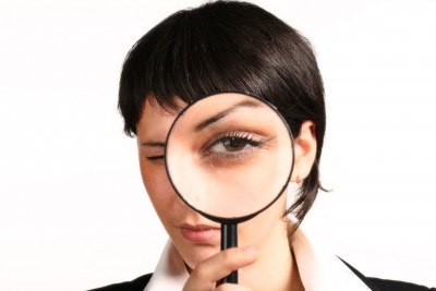 A professionally dressed woman holding a magnifying glass over her eye