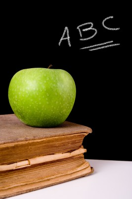 An apple on top of a book next to a chalk board