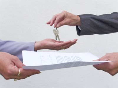 Two people exchaning a contract and a set of keys